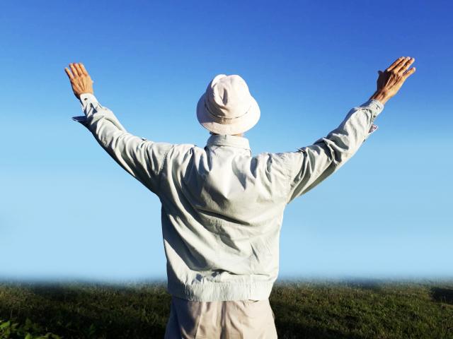 空と大地に向かって両手を大きく広げる健康なお年寄りの写真