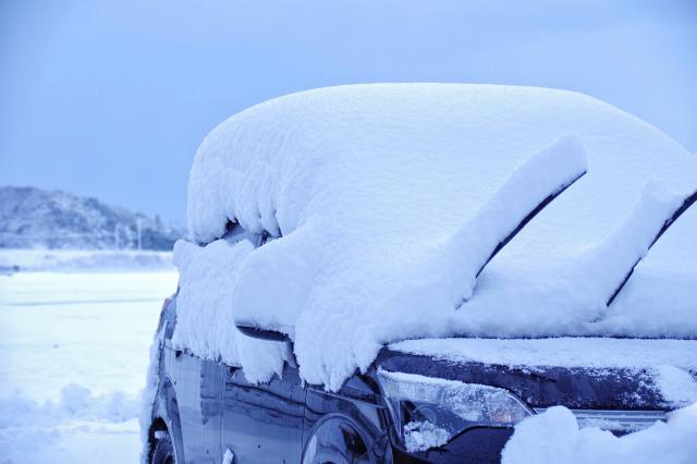 自動車に降り積もった雪。寒冷地の風景